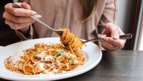 Una joven comiendo espaguetis.