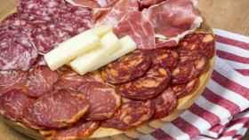 Un plato con embutidos y queso.