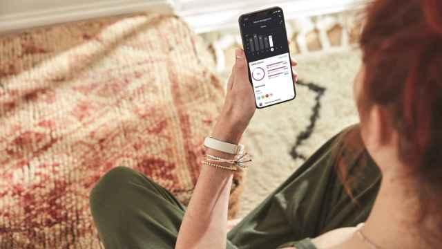 Una mujer con la pulsera de Fitbit, consultando sus datos personales en el smartphone
