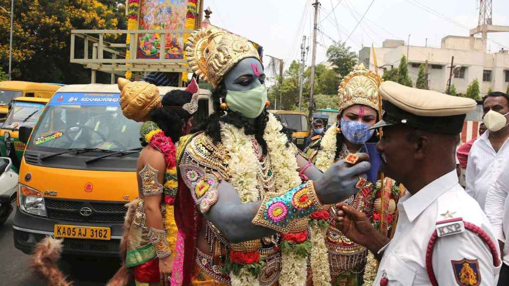 Figurantes caracterizados de dioses hindúes en una campaña por el uso de la mascarilla en Bangalore, India.