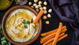 Un plato de barro con hummus y unos palitos de zanahoria.