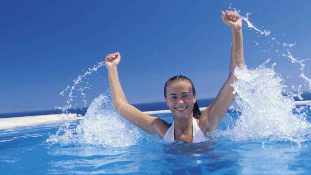 Una joven celebra en una piscina.