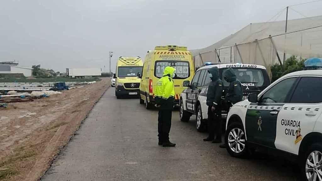 Un policía local y guardias civiles junto a la finca agrícola donde se produjo el accidente laboral.