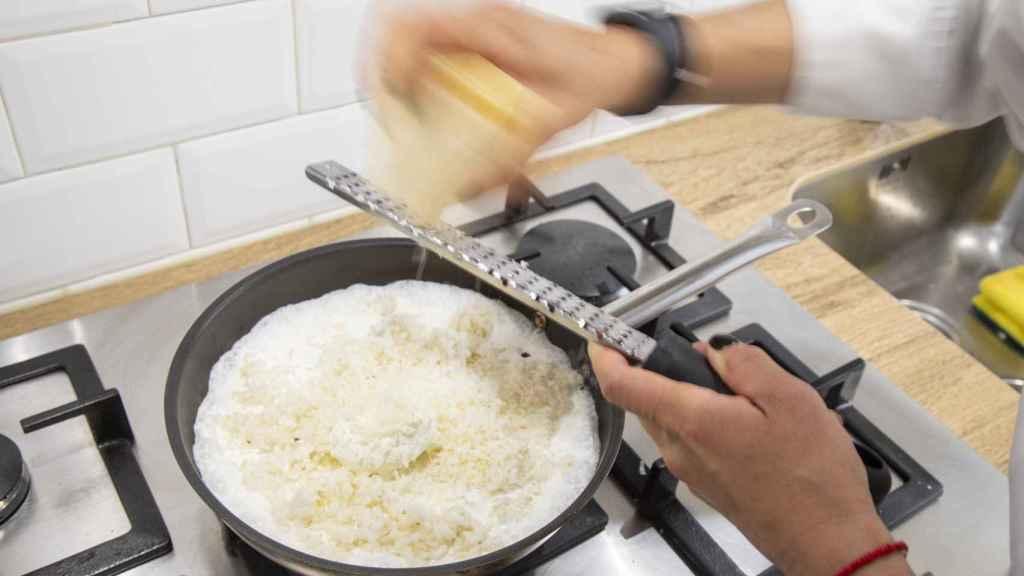 La chef Bárbara, antes de añadir las espinacas trituradas, ralla queso parmigiano en el risotto.