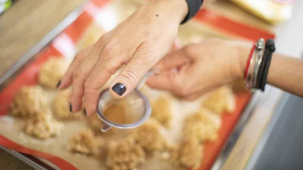 Bárbara espolvorea, con un pequeño colador, la canela molida sobre las galletas de arroz recién hechas.