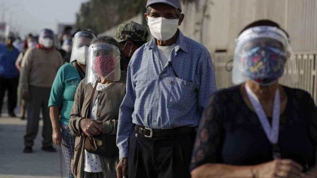 Varios peruanos esperan para acceder a un centro de votación en Lima.