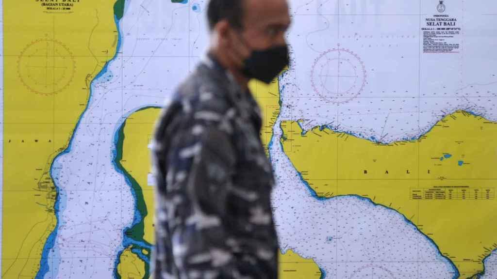 Un miembro de la armada indonesia ante un mapa de búsqueda del submarino.