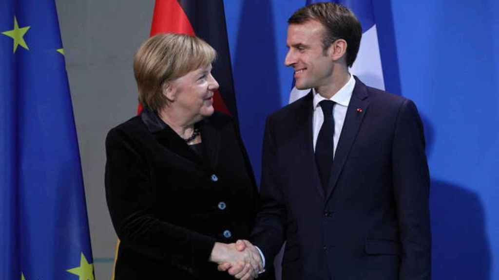 La canciller alemana, Angela Merkel, y el presidente francés, Emmanuel Macron, se dan la mano.