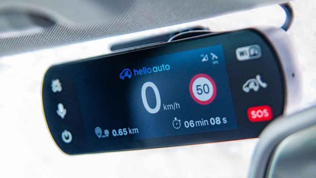 Imagen del dispositivo Hello Auto Connect colocado en el retrovisor de un vehículo.