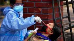 Una sanitaria india realizando una PCR.