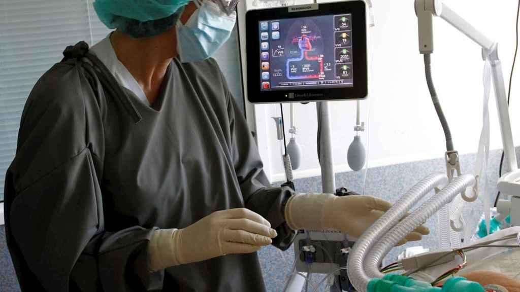 Una sanitaria atiende a un paciente con COVID-19 en el Complejo Hospitalario Universario de Ferrol. EFE/Kiko Delgado