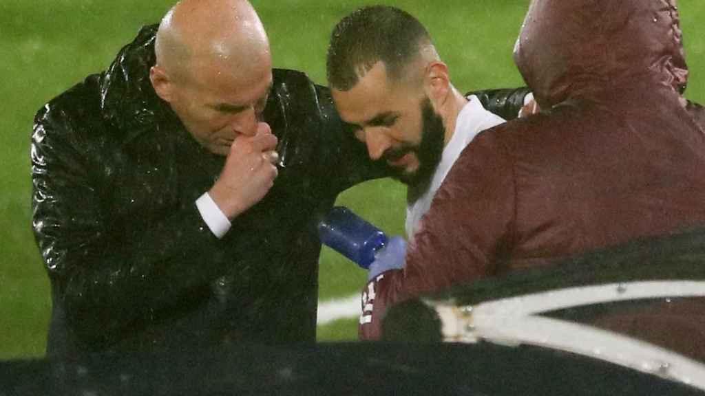 Zinedine Zidane habla con Karim Benzema tras ser sustituido ante el Chelsea