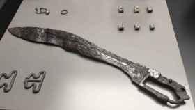 La falcata íbera, fechada en el siglo II a.C., recién restaurada, y otros objetos hallados en la tumba.