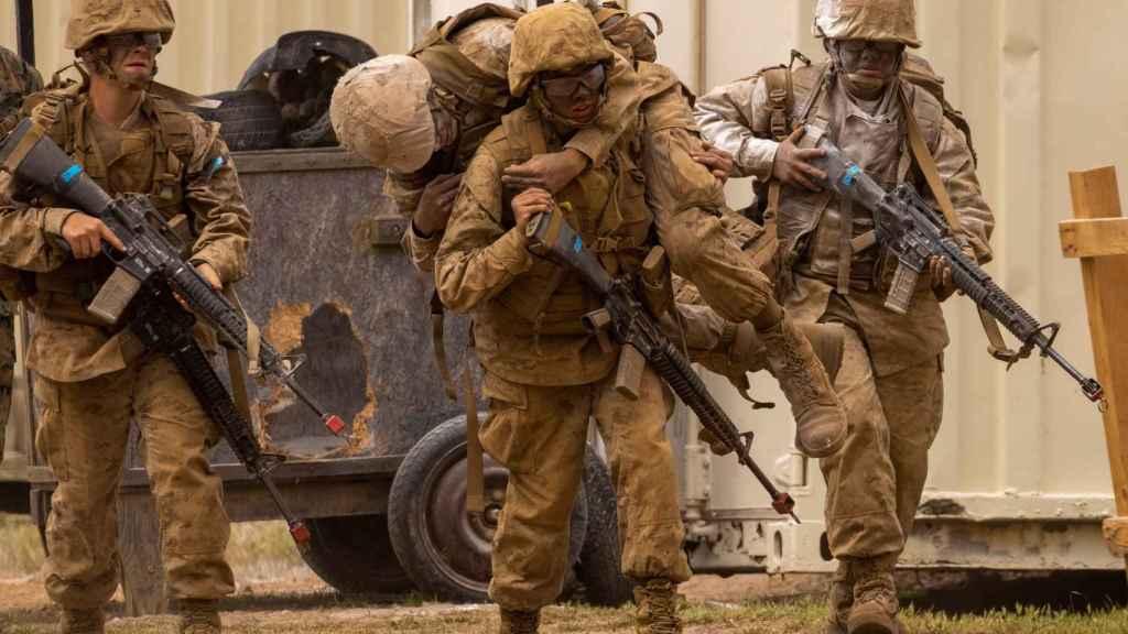 Reclutas de la Marina de Estados Unidos sostienen a sus compañeros durante la prueba del crisol.