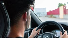 Un conductor con auriculares mientras conduce.