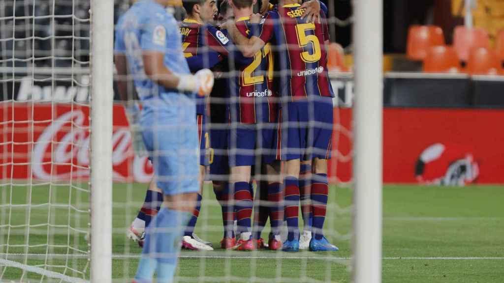 Cillessen (Valencia) observa mientras los jugadores del Barça celebran su gol