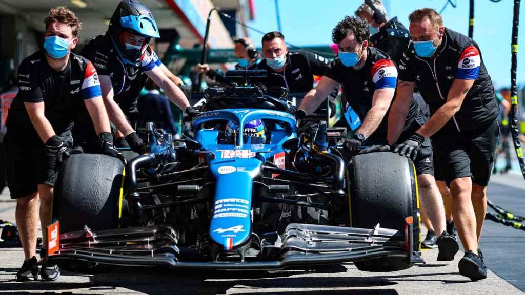 Fernando Alonso ayudado por sus mecánicos en Portimao