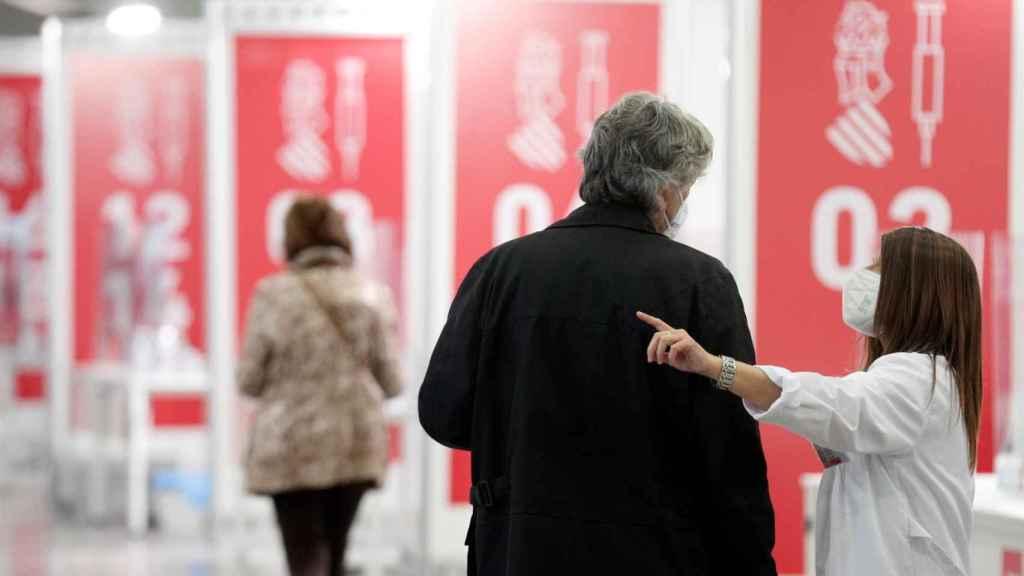 Una sanitaria de la Comunidad Valenciana da indicaciones a una persona que se va a vacunar.