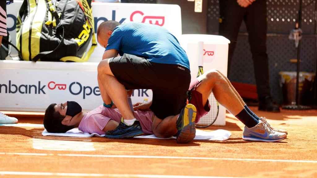 Carlos Alcaraz siendo atendido en el choque frente a Rafa Nadal en el Mutua Madrid Open
