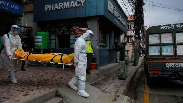 Miembros del Ejército de Nepal transportan un muerto por Coronavirus en Katmandú.