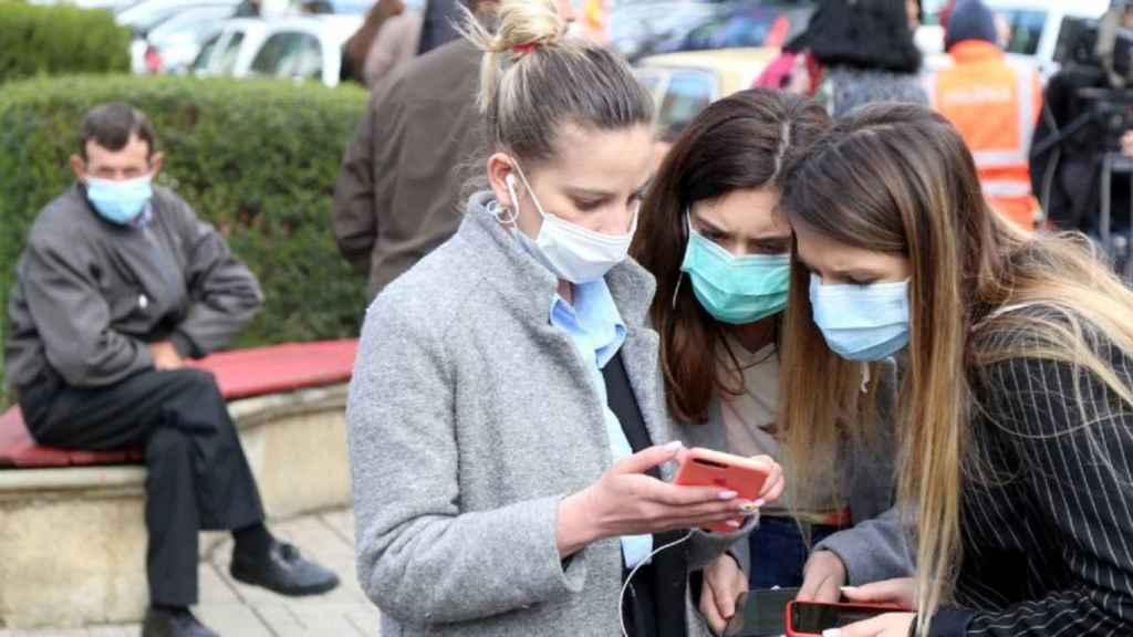 Unas jóvenes mirando su móvil.