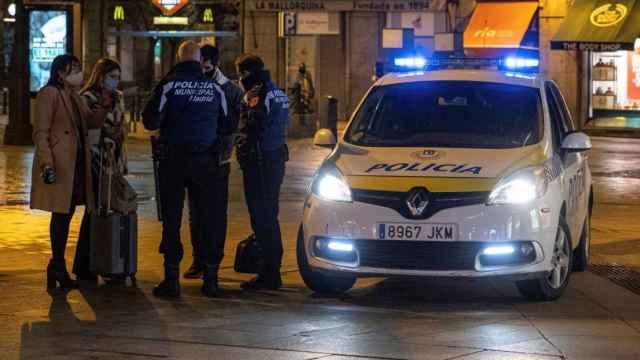 Dos policías municipales paran a viandantes en la Puerta del Sol de Madrid. Efe