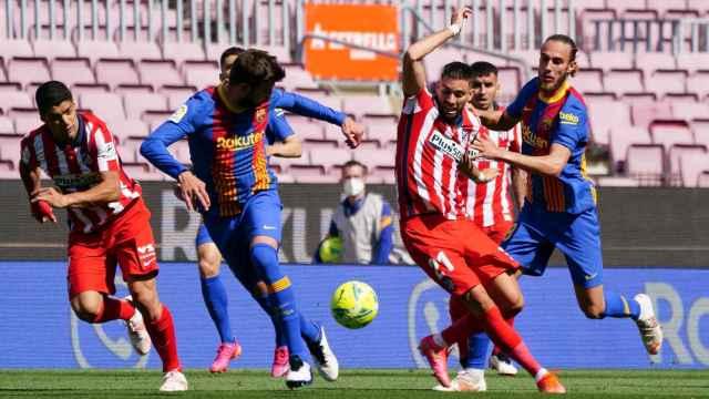 Carrasco (Atlético) intentando llevarse un balón ante Piqué y Mingueza (Barça)