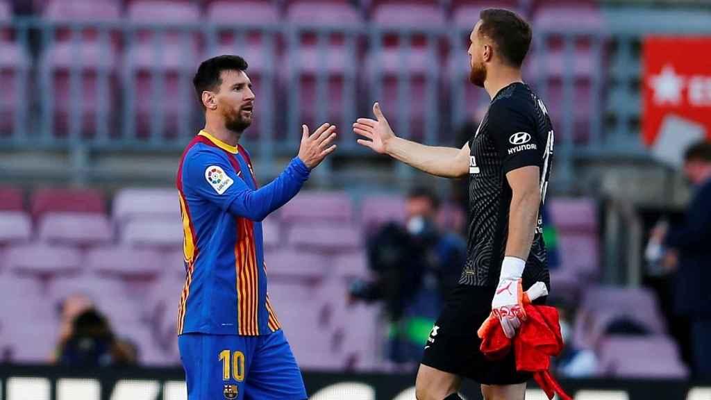 Oblak se saluda con Leo Messi
