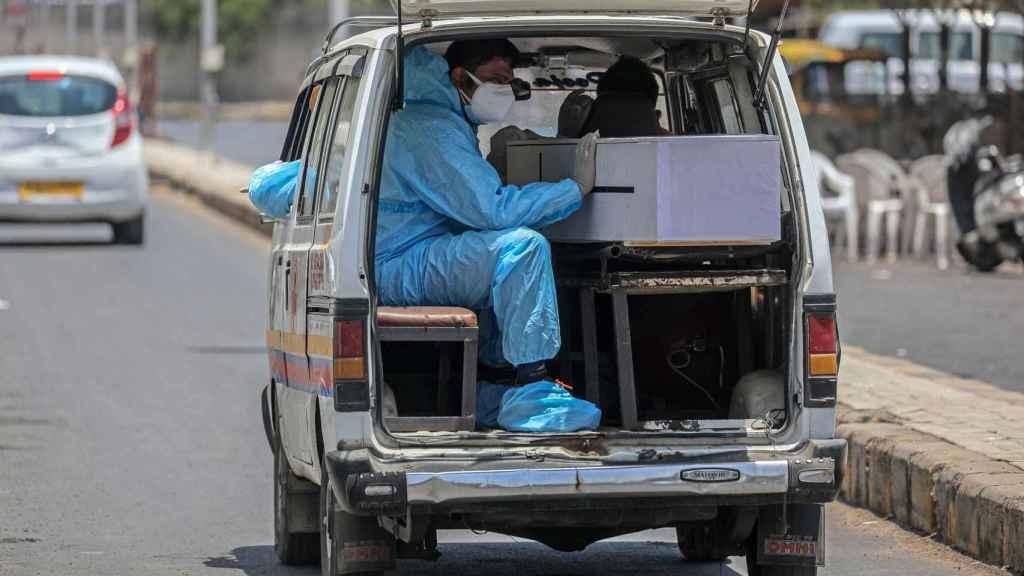 Un trabajador sanitario en una furgoneta que transporta un fallecido en Ahmedabad, India.