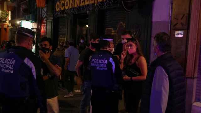 Varios agentes de policía advirtiendo de las medidas de seguridad a los jóvenes.