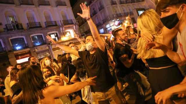 Un grupo de jóvenes celebra el fin del estado de alarma en la Puerta del Sol, en Madrid.
