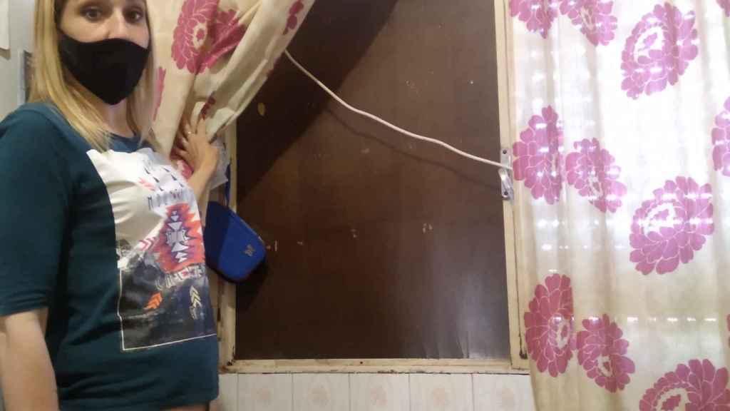 Jéssica mostrando una ventana cerrada con una lámina de madera de la casa que le cedieron tras los terremotos.