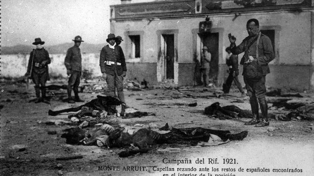 Un capellán reza ante los restos de los españoles encontrados muertos en Monte Arruit.