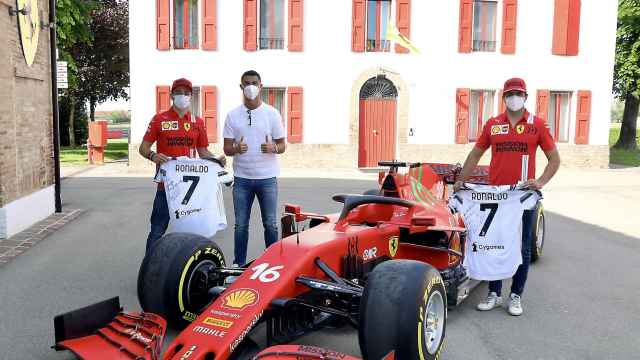 Charles Leclerc, Cristiano Ronaldo y Carlos Sainz posando con un Ferrari