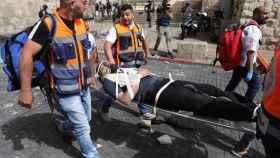 Trabajadores médicos evacuan a un hombre herido en la Puerta de los Leones.