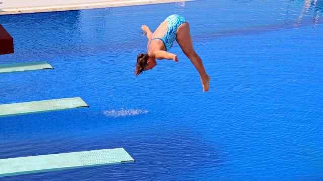 Una chica se lanza a una piscina desde un trampolín.