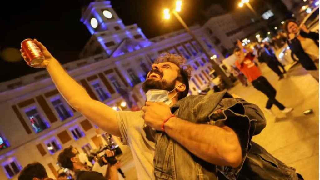 Un hombre brinda por el fin del estado de alarma en la Puerta del Sol de Madrid.
