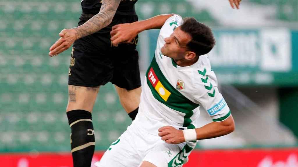 El delantero del Alavés, Joselu (i) pelea un balón con el defensa del Elche, Dani Calvo, durante el partido de Liga en Primera División.
