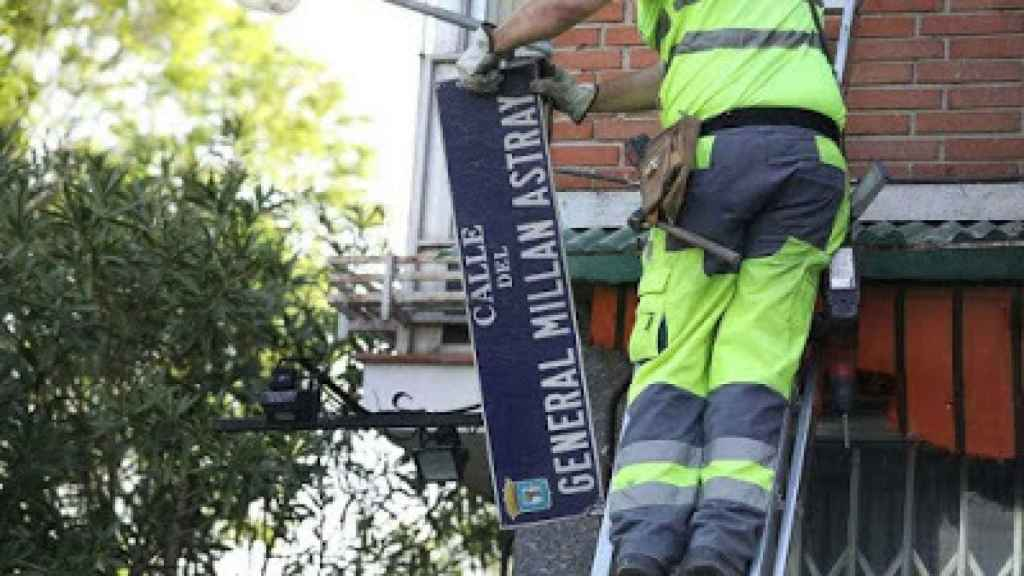 Momento en el que un trabajador municipal retira la placa de la calle en honor al general Millán-Astray.