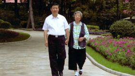 Xi Jinping camina junto a su madre, Qi Xing.