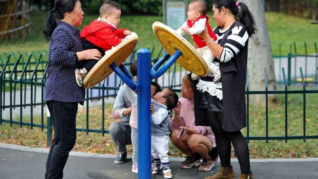 Tres mujeres juegan con varios niños pequeños en un parque.