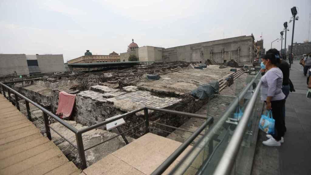Varias personas observan la zona arqueológica del Templo Mayor hoy, en Ciudad de México.