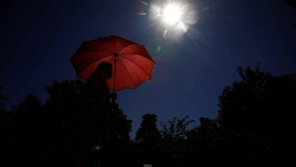 Una joven pasea bajo el sol con un paraguas.