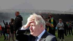 Boris Johnson, Primer Ministro de Reino Unido, con los altercados en Old Trafford de fondo