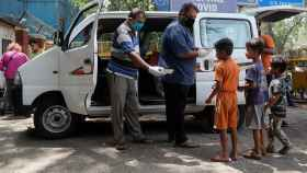 La gente distribuye comida a los niños fuera de un centro de cuidado en Shehnai (India).