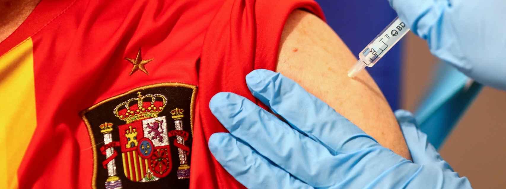 Un hombre con la camiseta de la Selección recibe la vacuna de AstraZeneca.