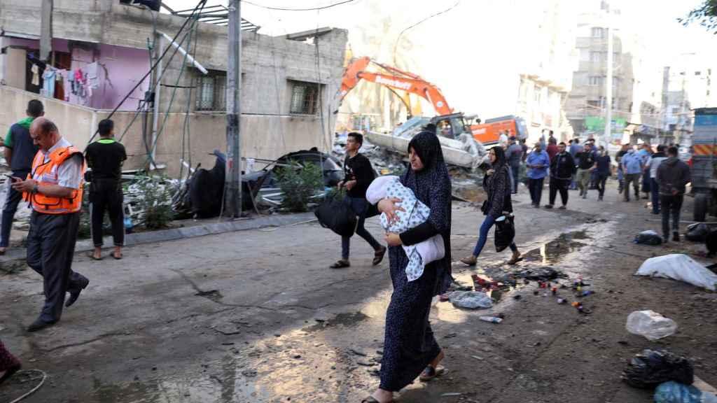 Una mujer lleva a su bebé durante los rescates en Gaza.