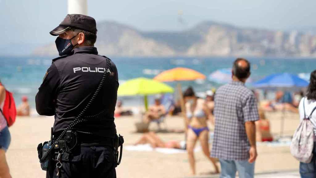 Un agente de Policía vigila la playa de Benidorm, este fin de semana.