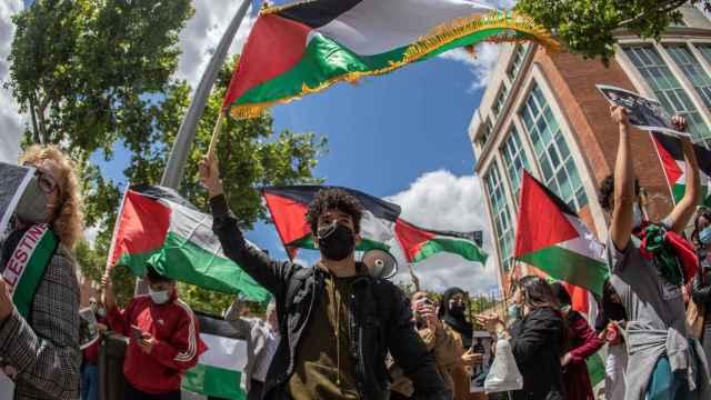 Varias personas ondean banderas del pueblo palestino frente a la Embajada de Israel en Madrid.