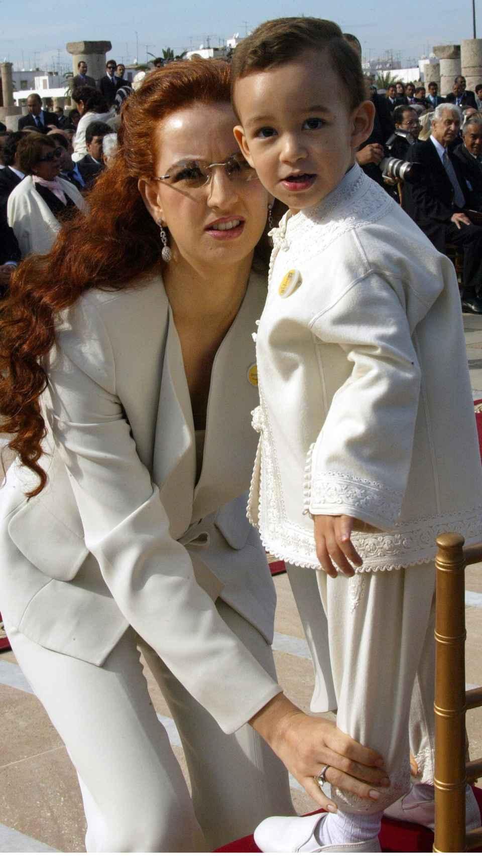 La princesa Lalla Salma arregla el atuendo de su hijo, el heredero Moulay Hassan.